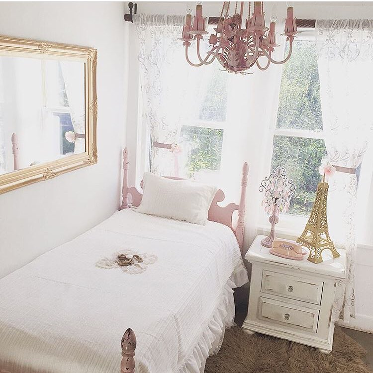 Girls bedroom with large gold mirror on wall and pink flower chandelier with white sheets and pink twin bed frame