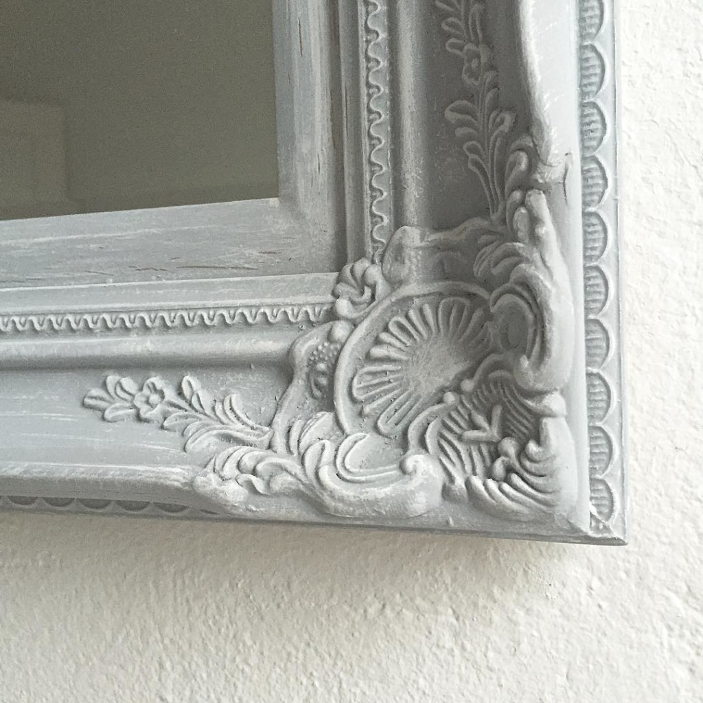 corner of large grey ornate mirror with slight white distressing