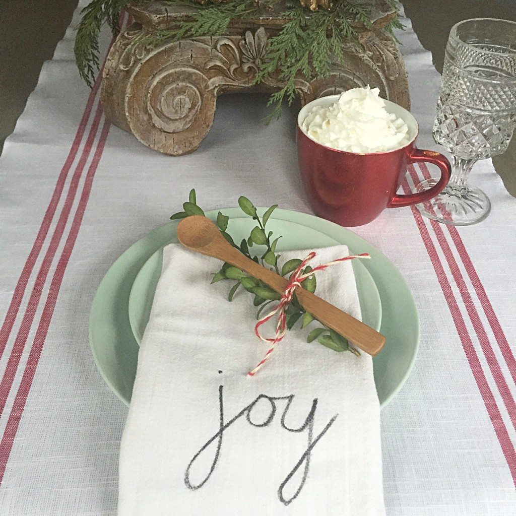 Green plate with folded napkin that says joy along with a cup of cocoa and whip cream