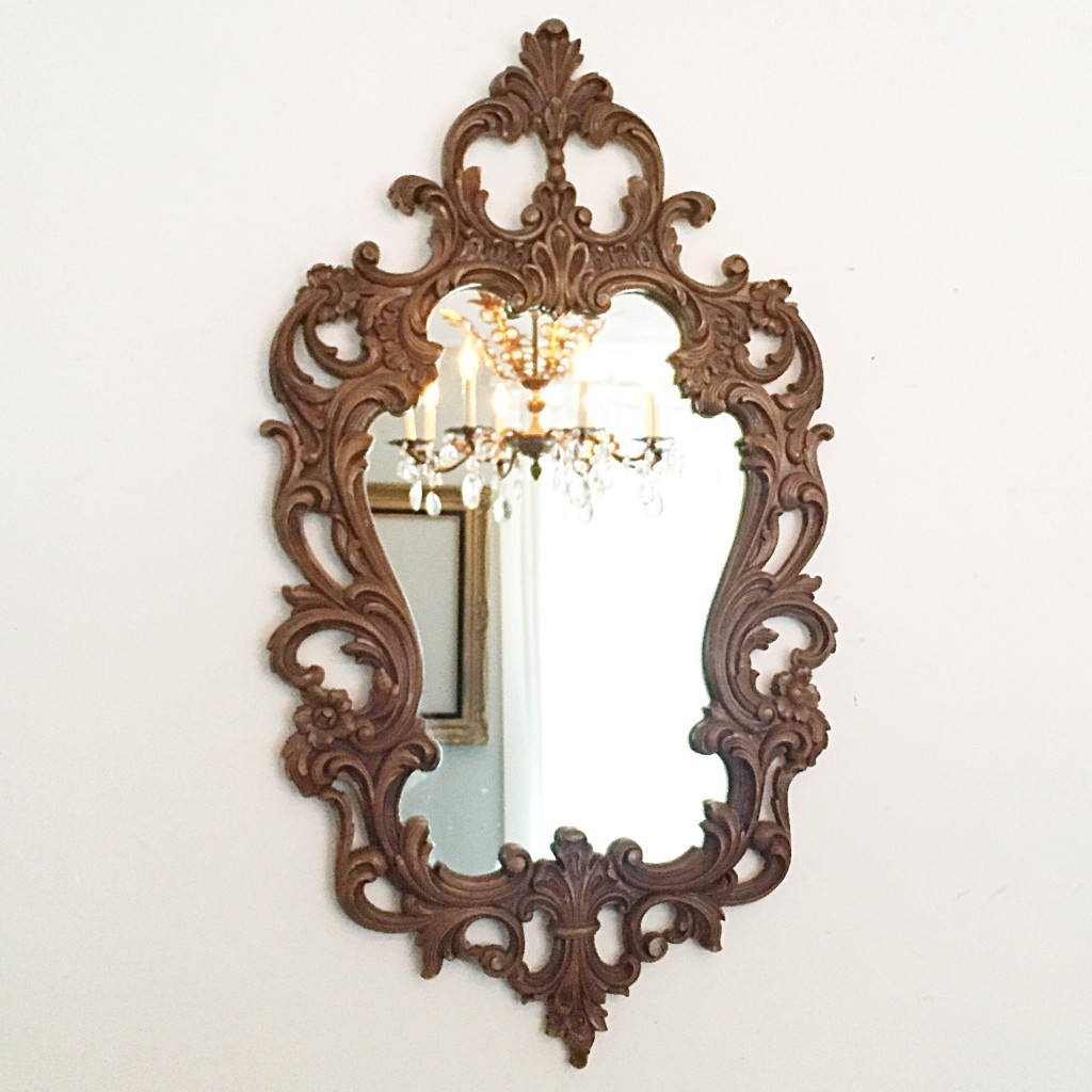 Ornate wood framed mirror with a crystal chandelier in the reflection