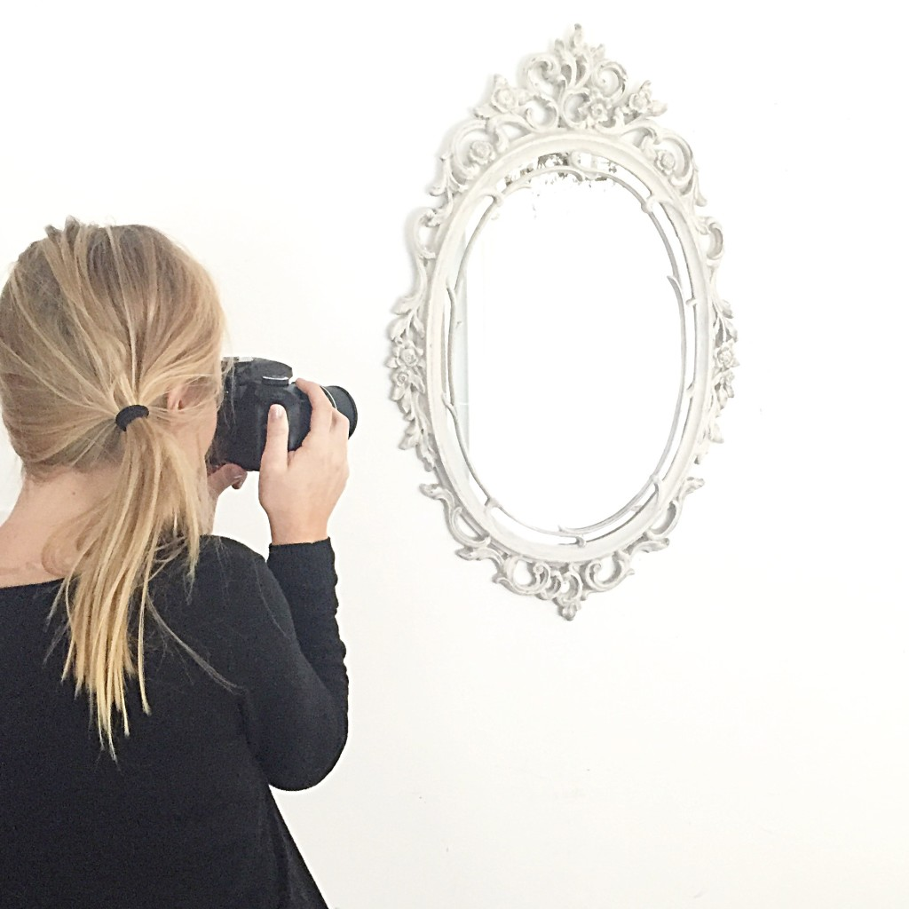 Blonde haired girl holding camera taking a picture of ornate white mirror