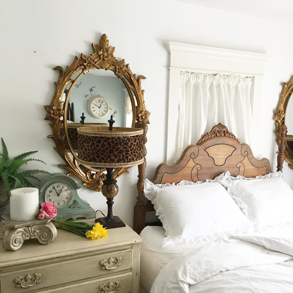 large gold mirror bedside with leapord lamp beside white linen bed