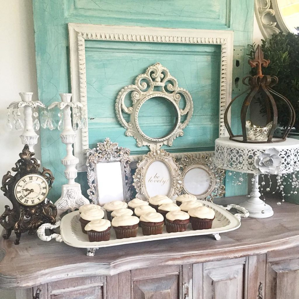 Vintage Girls Birthday Party Theme blue door with 5 white frames leaning and 2 white candle holders. white tall cake stand with rust crown and a white platter full of cupcakes