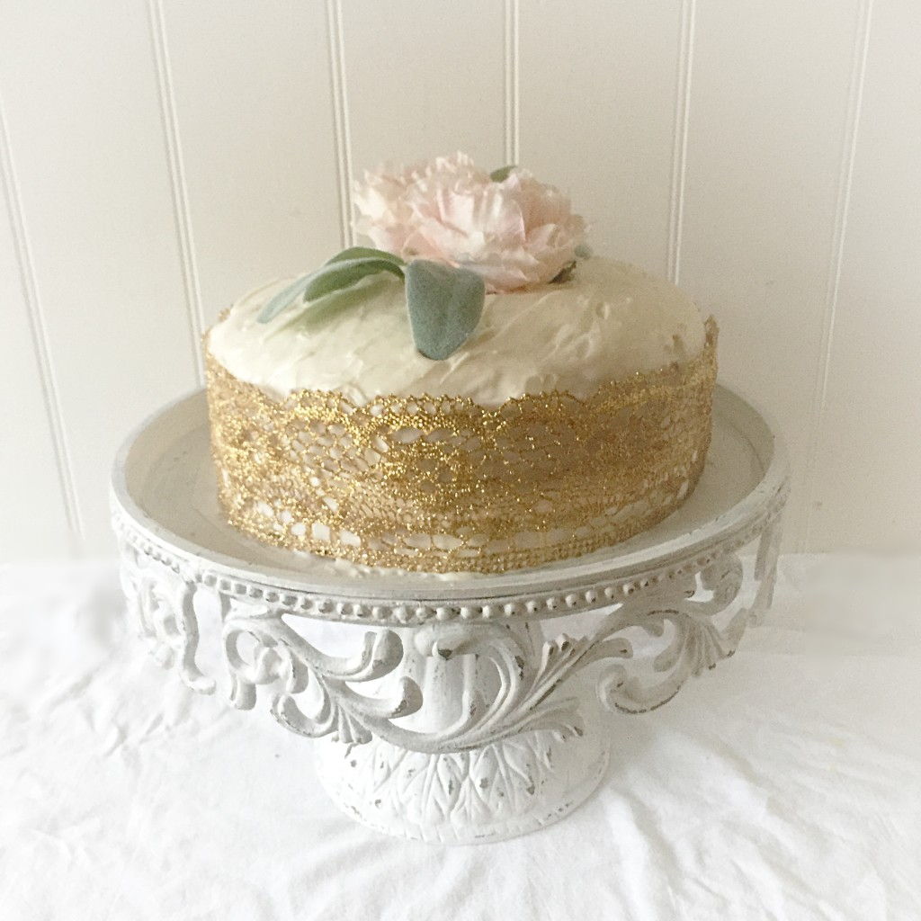 distressed white cake stand with white and gold cake with pink flower ontop