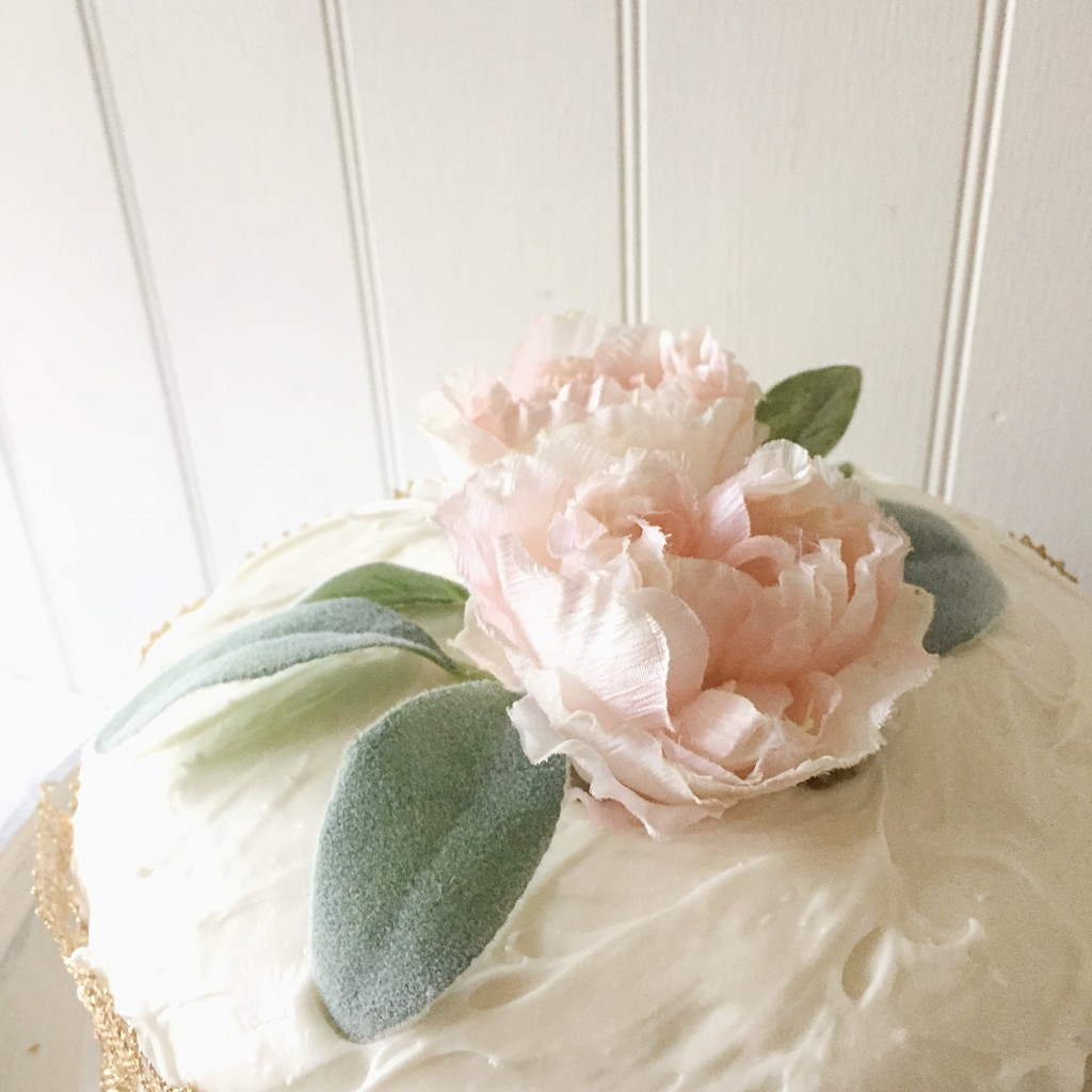 pink flower ontop of a white frosted cake