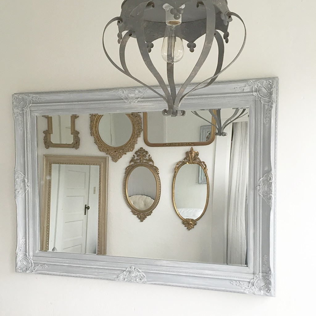 crown grey hanging light and large grey mirror with 6 gold mirrors in the reflection