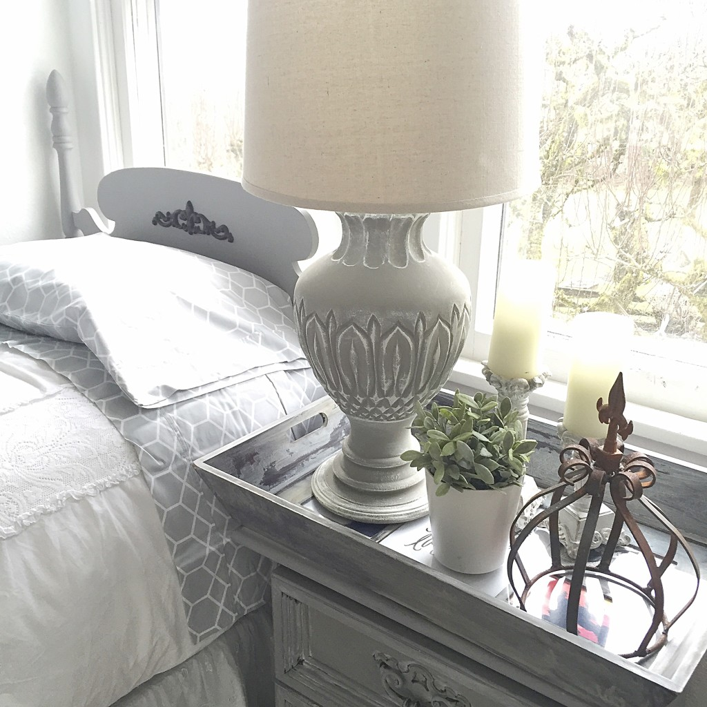 grey table lamp with white shade and rust french crown ontop of grey nightstand