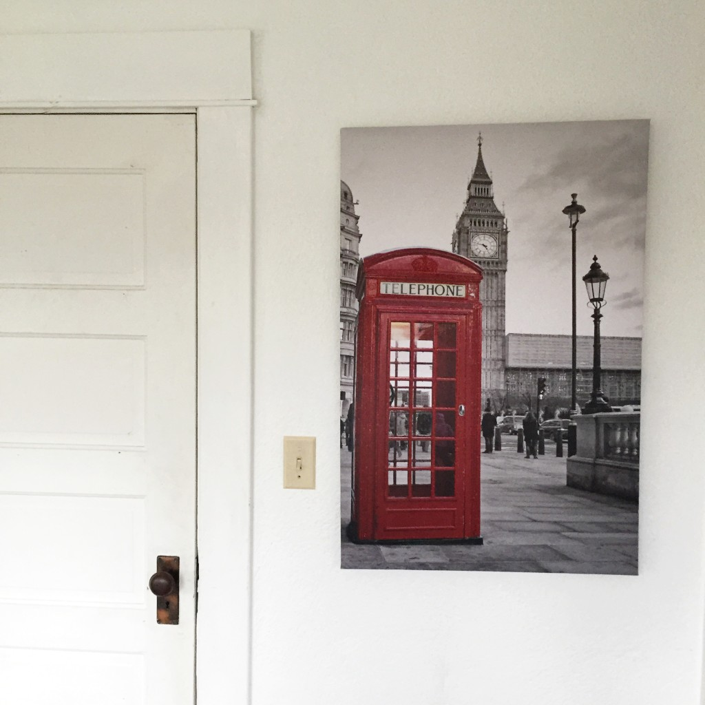farmhouse white door with a picture hanging next to it of red telephone booth
