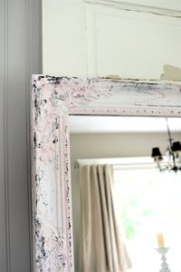 corner of pink ornate mirror distressed with white and black