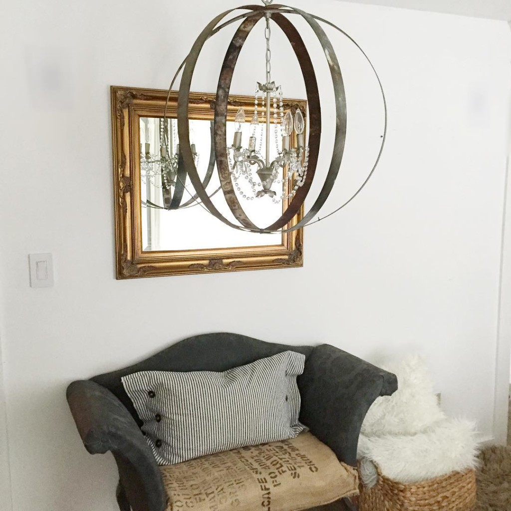metal orb chandelier light with gold mirror behind and small gray couch with ticking stripe pillow