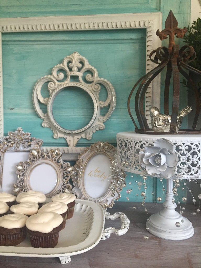 blue door with white farmes and white tray filled with cupcakes