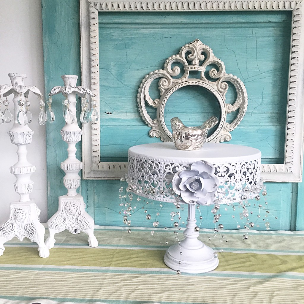 blue door white 2 white frames and white cake stand with 2 white candle holders