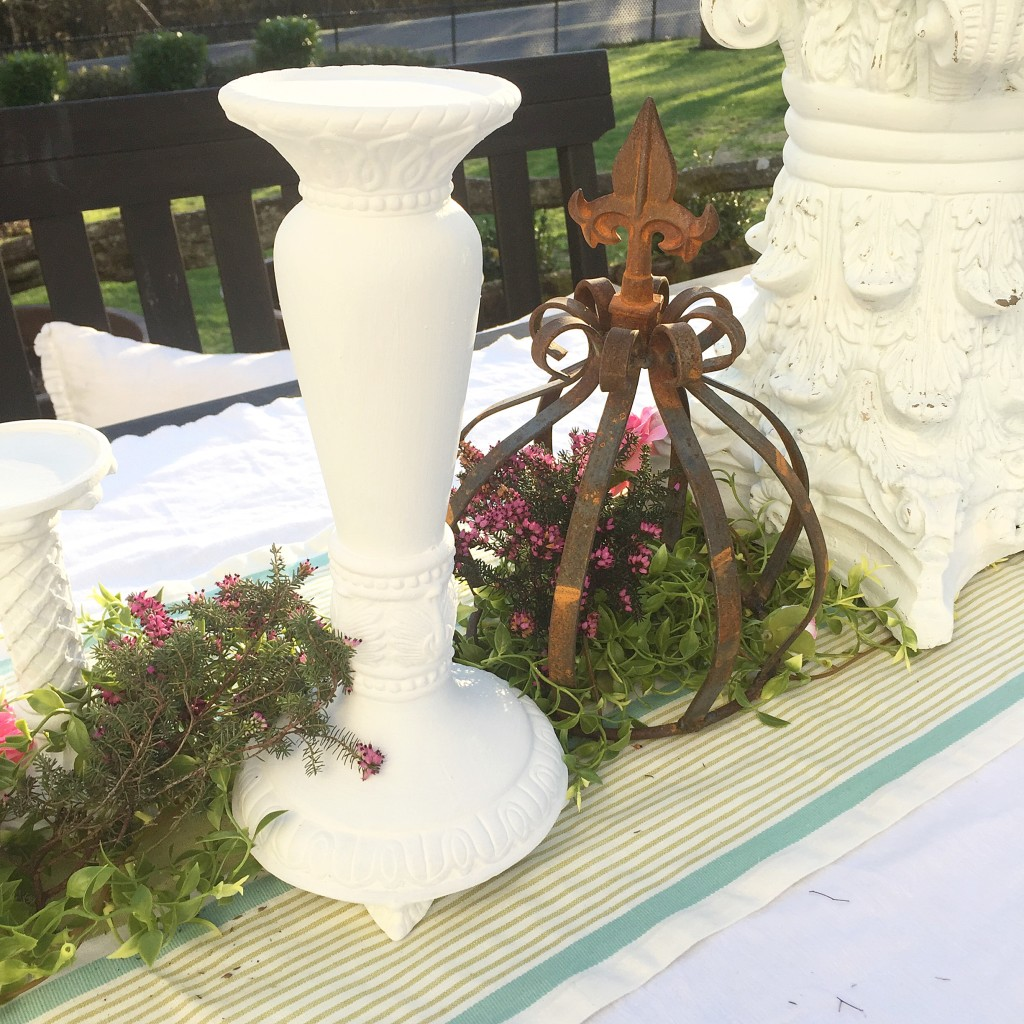 white candle holder with rust crown on top of greenery