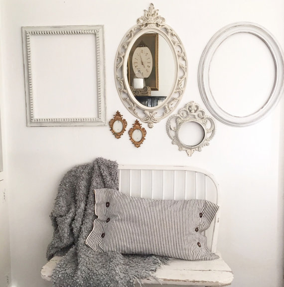 gallery wall with 3 white frames one white mirror and 2 mini gold frames with white bench below and ticking stripe pillow