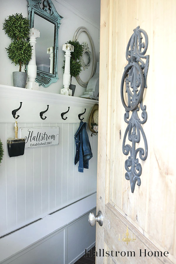 How to Decorate a Small Entryway door opeing into white mudroom with blue mirror and 2 white candle holders with black hooks