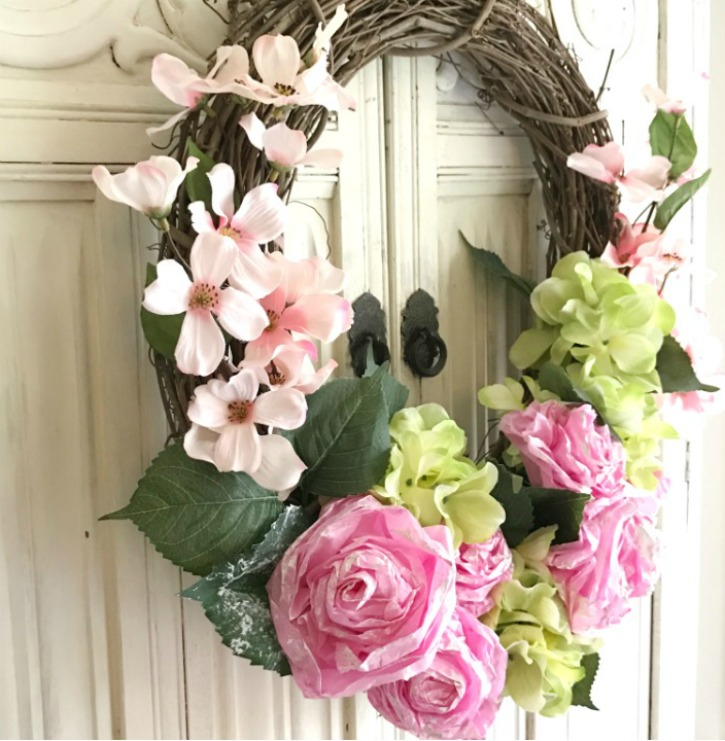 grapevine wreath with pink and green flowers against a white wall