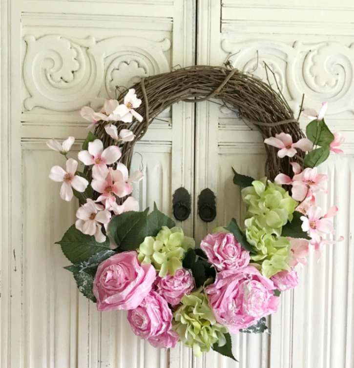DIY Tissue Paper Flower Wreath grapevine wreath with pink and green flowers with green leaves. haning against white wall