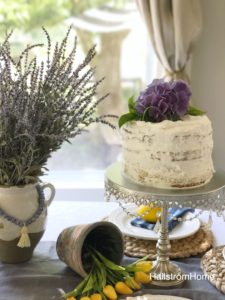 Frosted cake with fresh flowers on top and a cake stand with a vase of lavender next to it