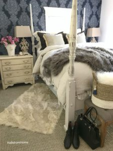 queen canopy bed with blue wallpaper and white fur rug with black boots and purse at edge of bed with grey fur blanket on top of white sheets