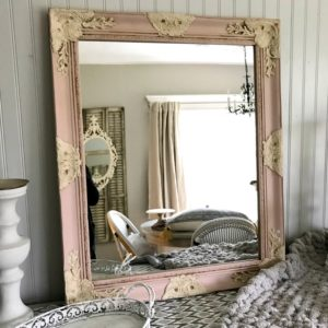 Pink and cream framed mirror with a chunky knit throw blanket