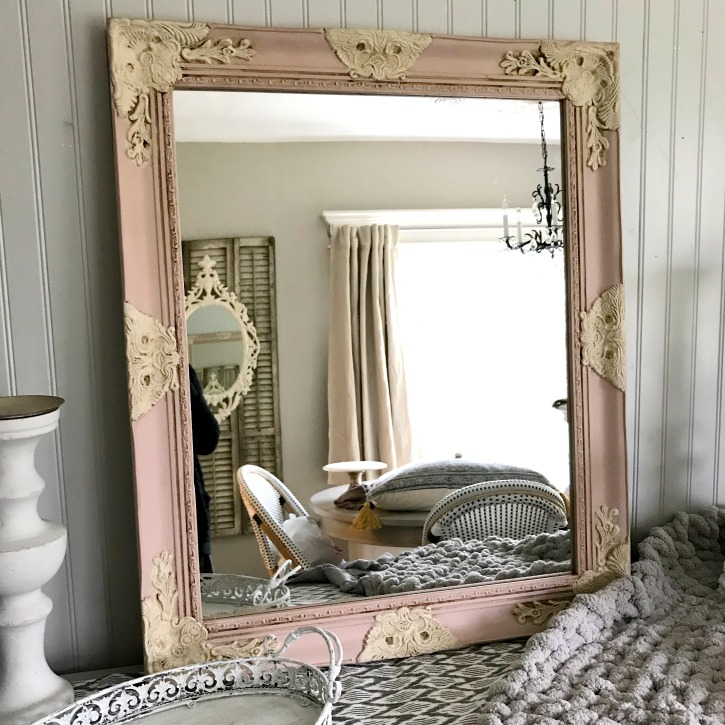 Pink and cream mirror with white candle holders by it and thick knit gray blanket