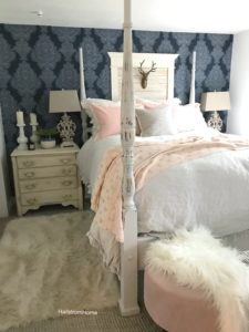 Canopy bed with pink throw blanket and pink pillows with a white fur rug