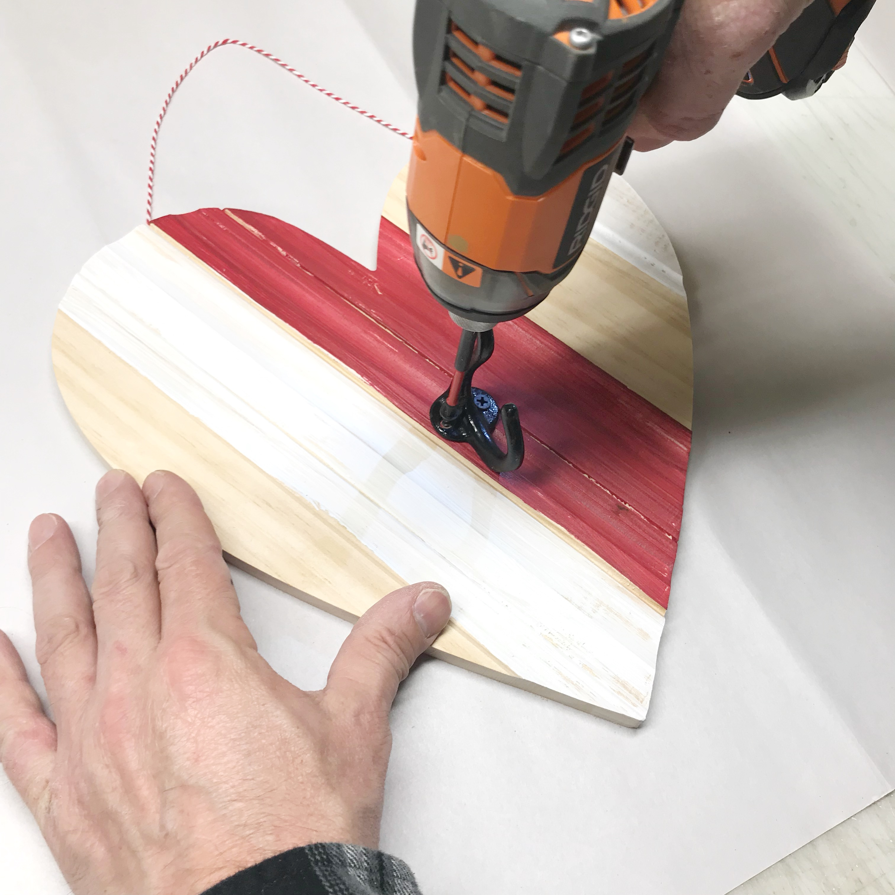 Drilling coat hook into striped heart shaped wall decor