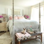 13 Tips for Making a Cozy Bedroom Retreat with bedroom view of white bedding with 2 pink linen pillows and 2 bouquets of pink orchids on each side of bed