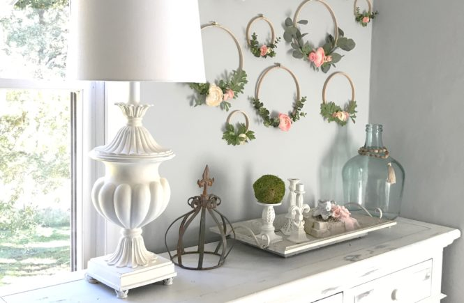 Making Hoop Wreaths for Spring with 10 embroidery hoops with flowers and greenery on wall above white dresser