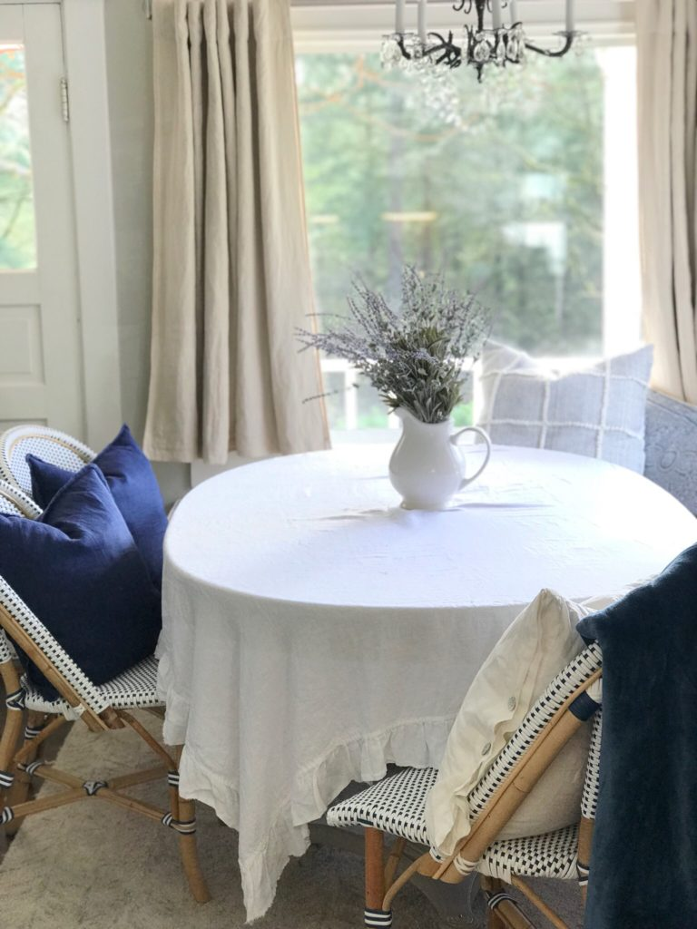white ruffle linen table cloth with white pitcher filled white lavender and 3 chairs with 2 navy blue pillows