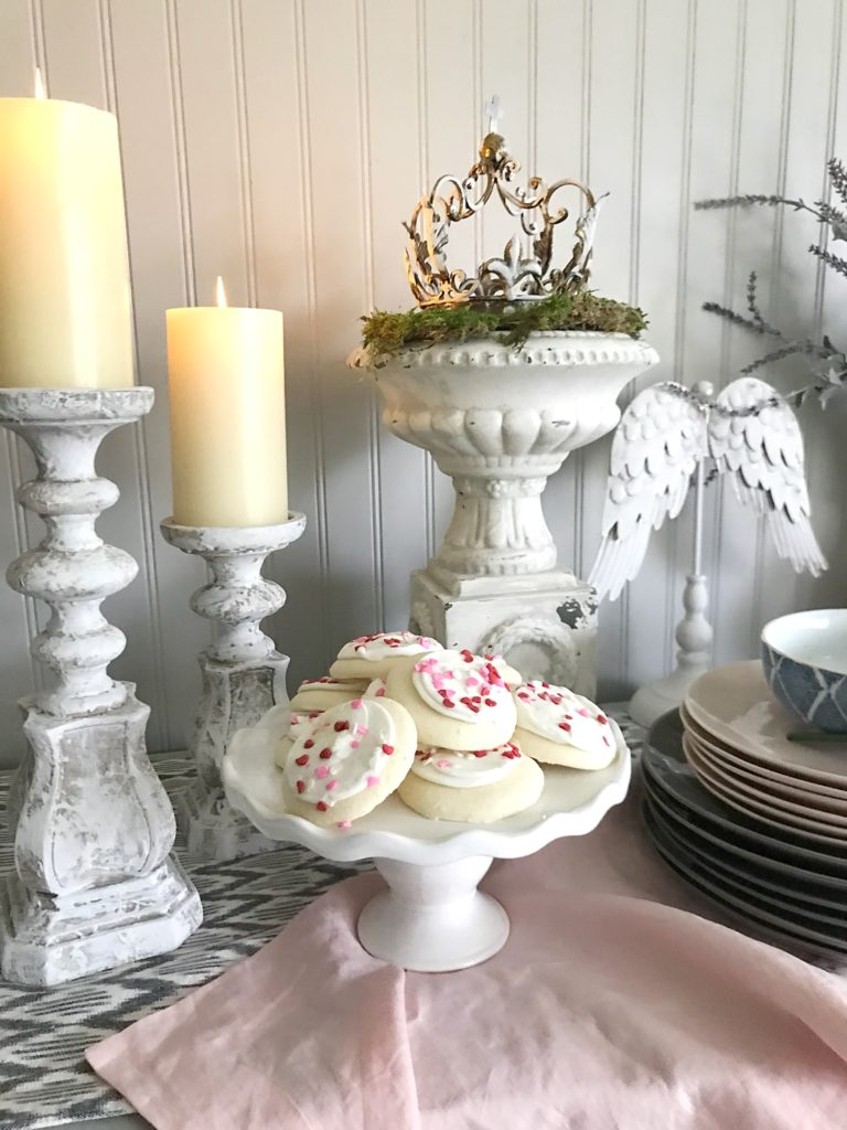 white serving platter with lots of cookies and 2 white distressed candle holders ontop of pink linen table runner and a stack of pink and grey plates next to cookies