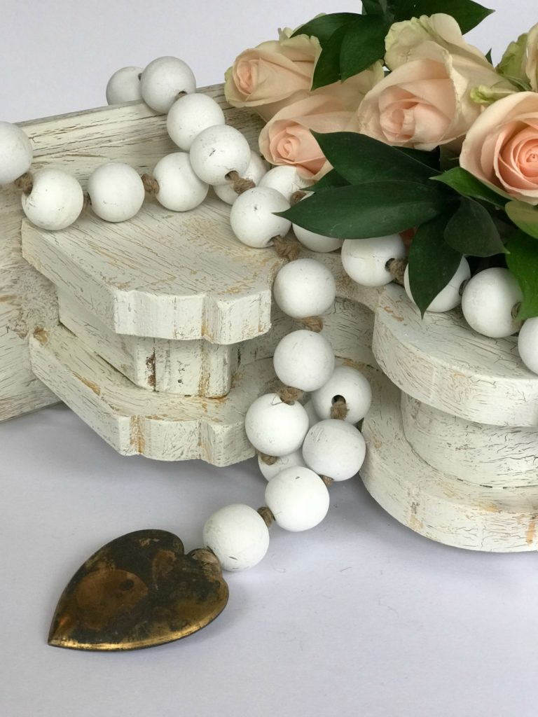 How to Make White Wood Bead Garland a white chippy corbel with white wood bead garland draped ontop. bead garland has metal heart at the end and pink roses set ontop of corbel