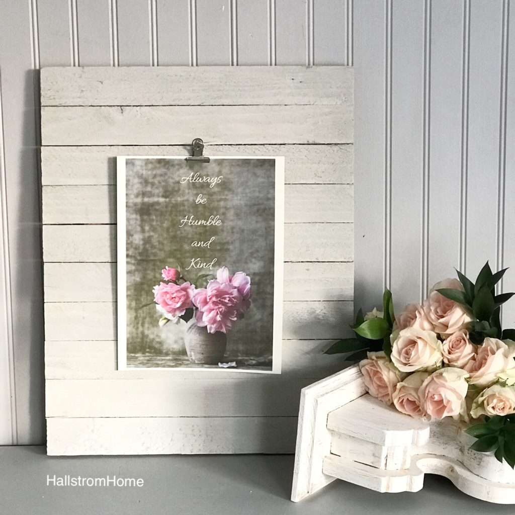 white wood board leaning with pink flower printable and white corbel nest to it with pink roses