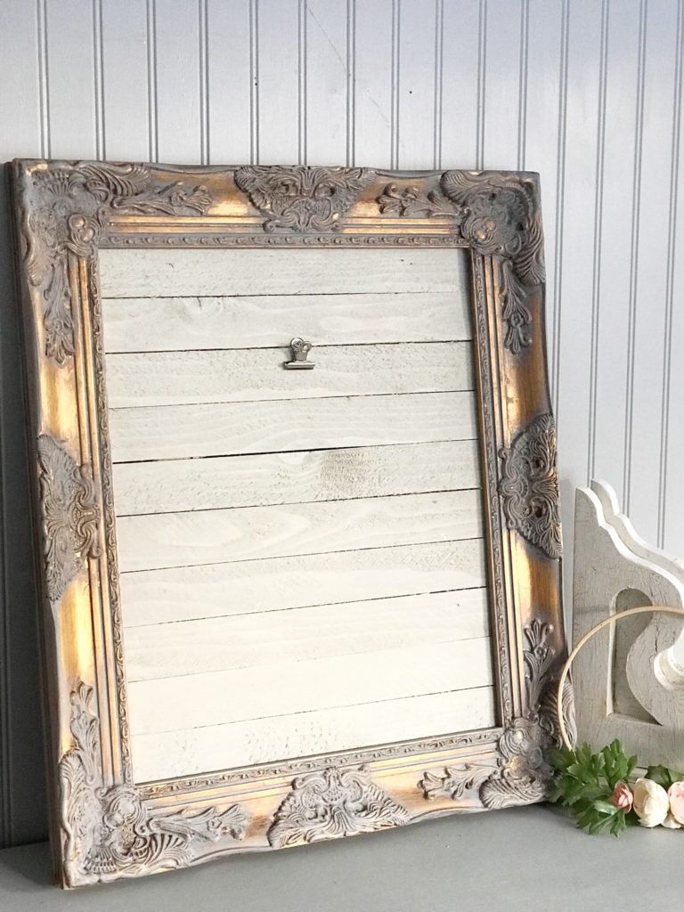 white wood with gray and gold frame framing wood. White corbel and the side of leaning frame