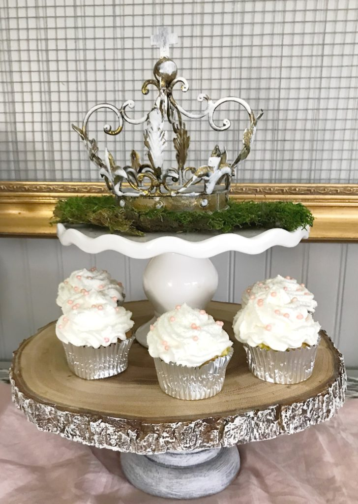 french crown on white cake stand ontop of wood cake stand with 5 white frosted cupcakes