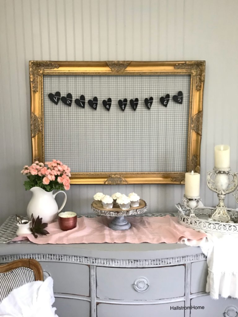 gold ornate frame with chicken wire and valentines heart banner with cupcakes and pink flowers displayed. pink linen table runner and 3 candle holders