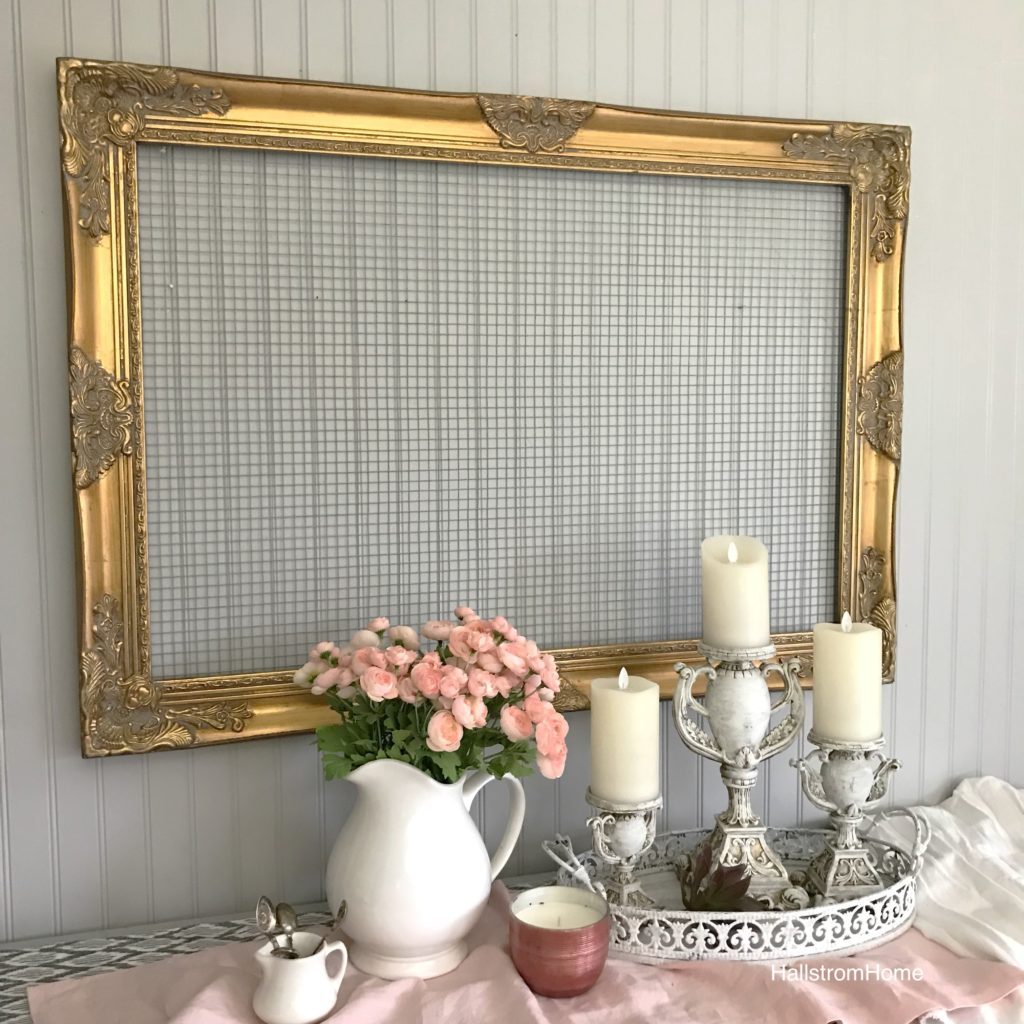 Gold ornate frame with chicken wire hanging. white pot of pink flowers and 3 candles with a pink linen table runner and pink candle
