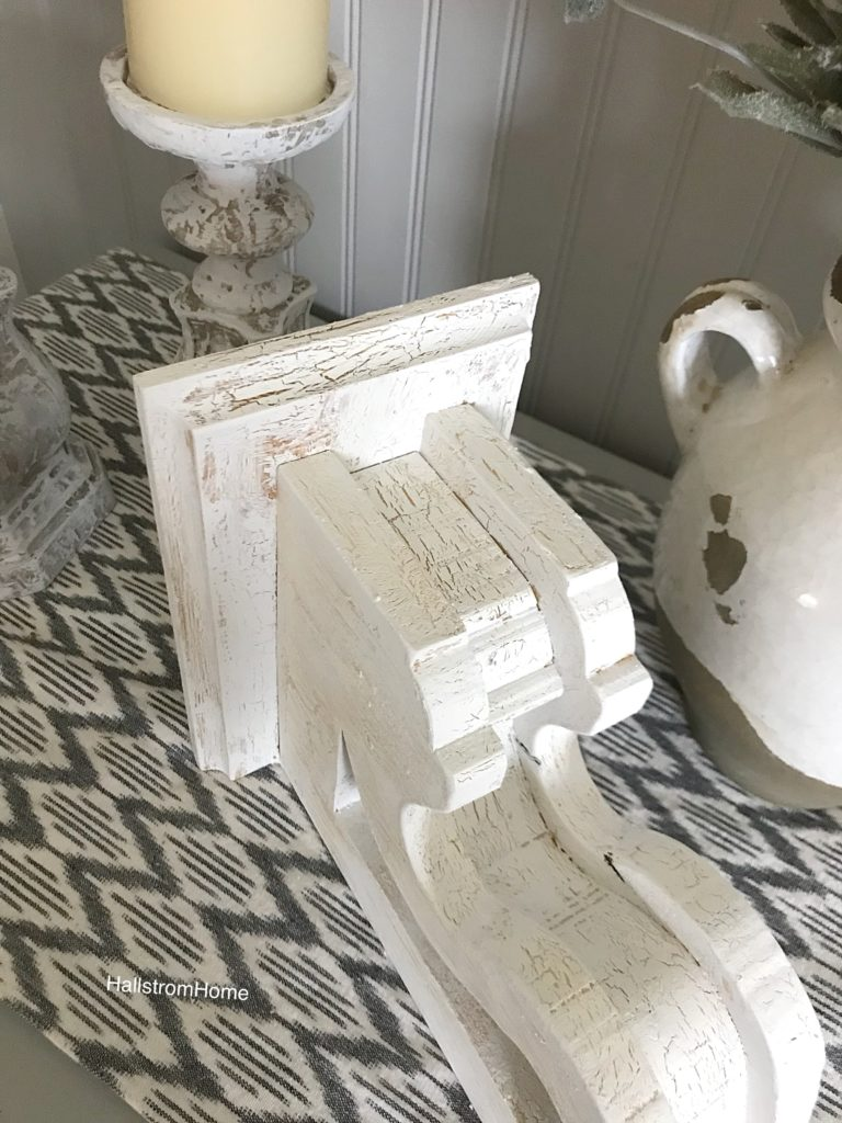 chippy painted white corbel on a patterned blue table runner and 2 white candle holders on the left and a white pot on the right
