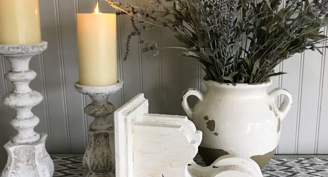 How to Chippy Paint Corbels white corbel on its side with 2 white distressed candle holders with cream candles and white pot with lavendar