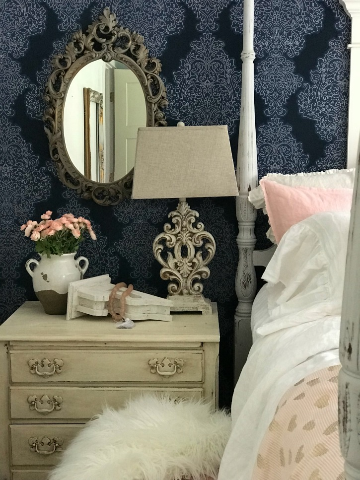 blue wall paper with brown ornate mirror hanging and night stand with ornate white table lamp and white vase with pink flowers and white chippy corbel with pink glass beads on it and white fur blanket on stool below