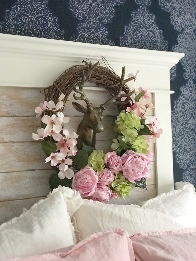 blue wallpaper and wreath hanging infront of covered window. wreath with pink and green flowers and gold deer head in the middle