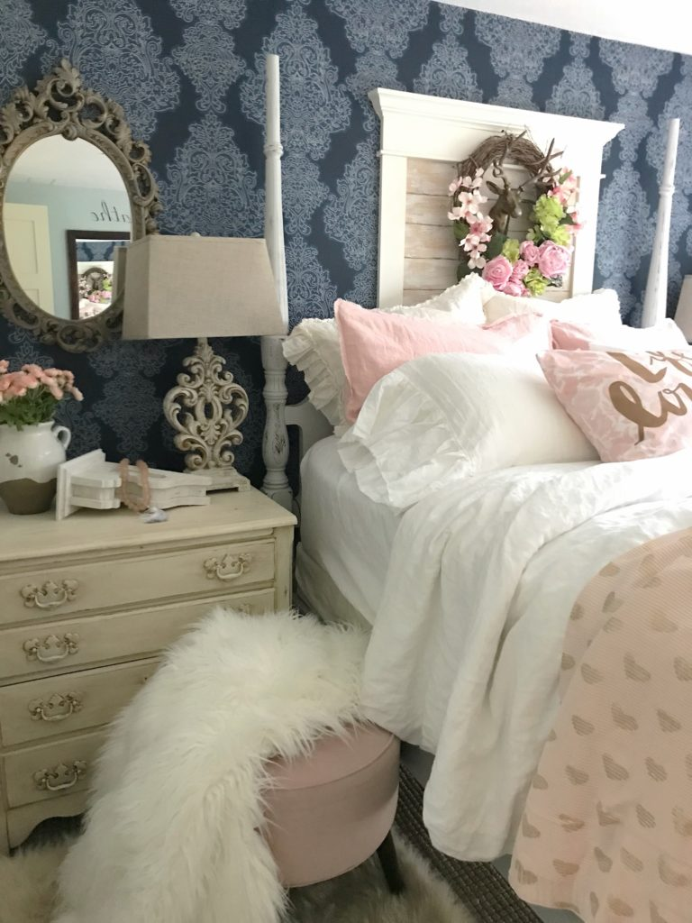 13 Tips for Making a Cozy Bedroom Retreat master bedroom with blue wallpaper and ornate mirror on left of bed above night stnad with ornate lamp and pink bouquet, pink foot stool with with fur blanket and white and pink bedding