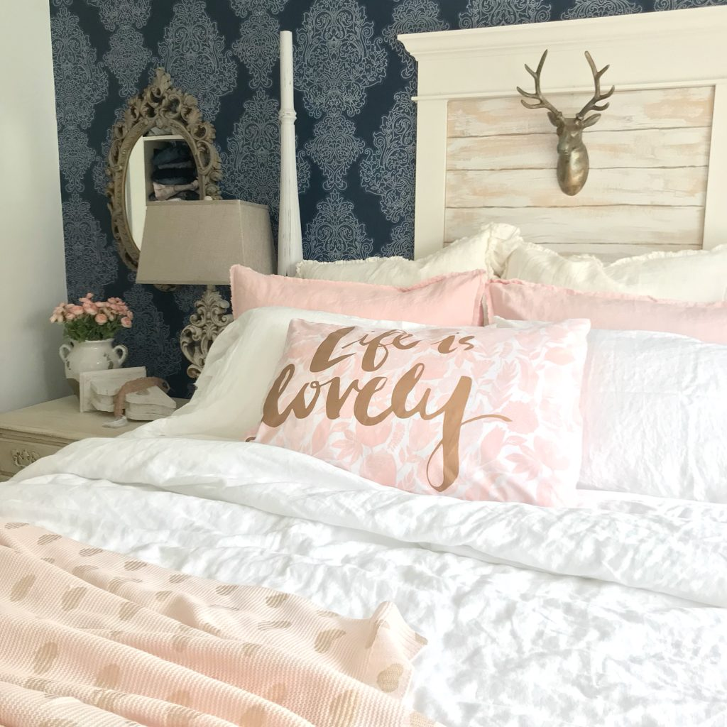 bedroom with blue wall paper and window with gold deer head behind bed. bed with 4 white linen pillows and 2 pink linen pillows and one accent pink pillow that says life is lovely