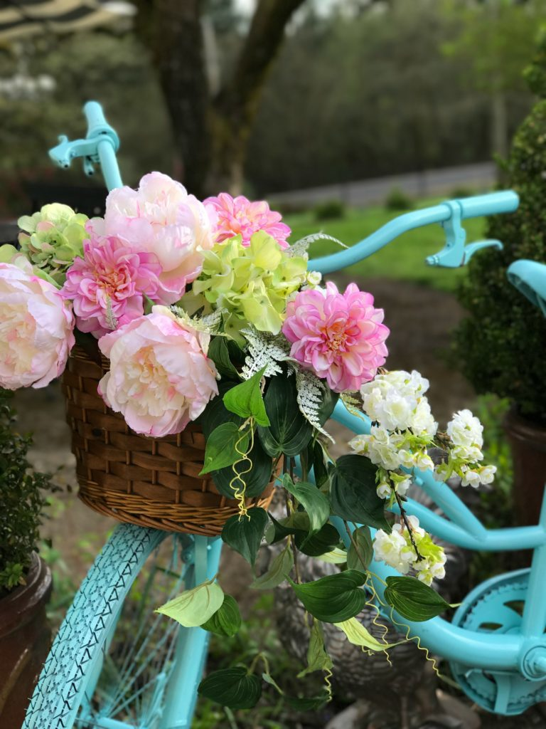 blue painted bike with wicker basket on fronr. filled with pink and green flowers