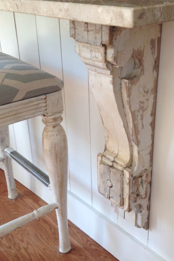 white chippy painted corbel under a marble counter with a bar chair thats white washed and has blue and white cushion