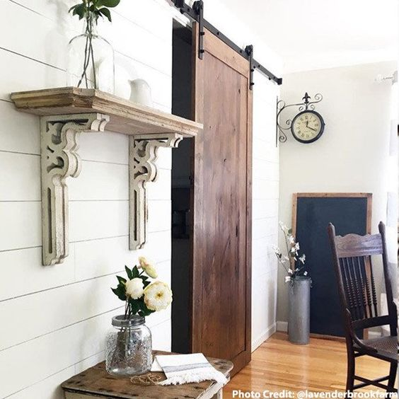 white corbels used as shelf. sliding barn door and under shelf little table with 3 white flowers in a large mason jar