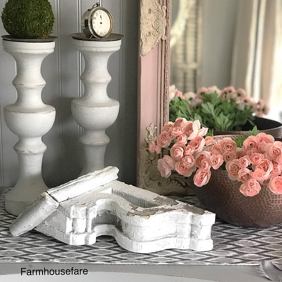 chippy white corbel with 2 candle holders and a copper bowl with pink flowers and a pink and white mirror behind that