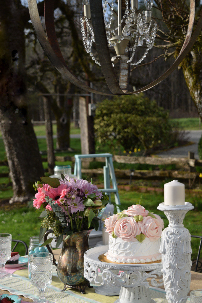 Easter Table Setting with Mini Cheesecakes white cake with pink frosted roses. tall white candle holder. outdoors with hanging chandelier silver vase on table with pink and purple flowers