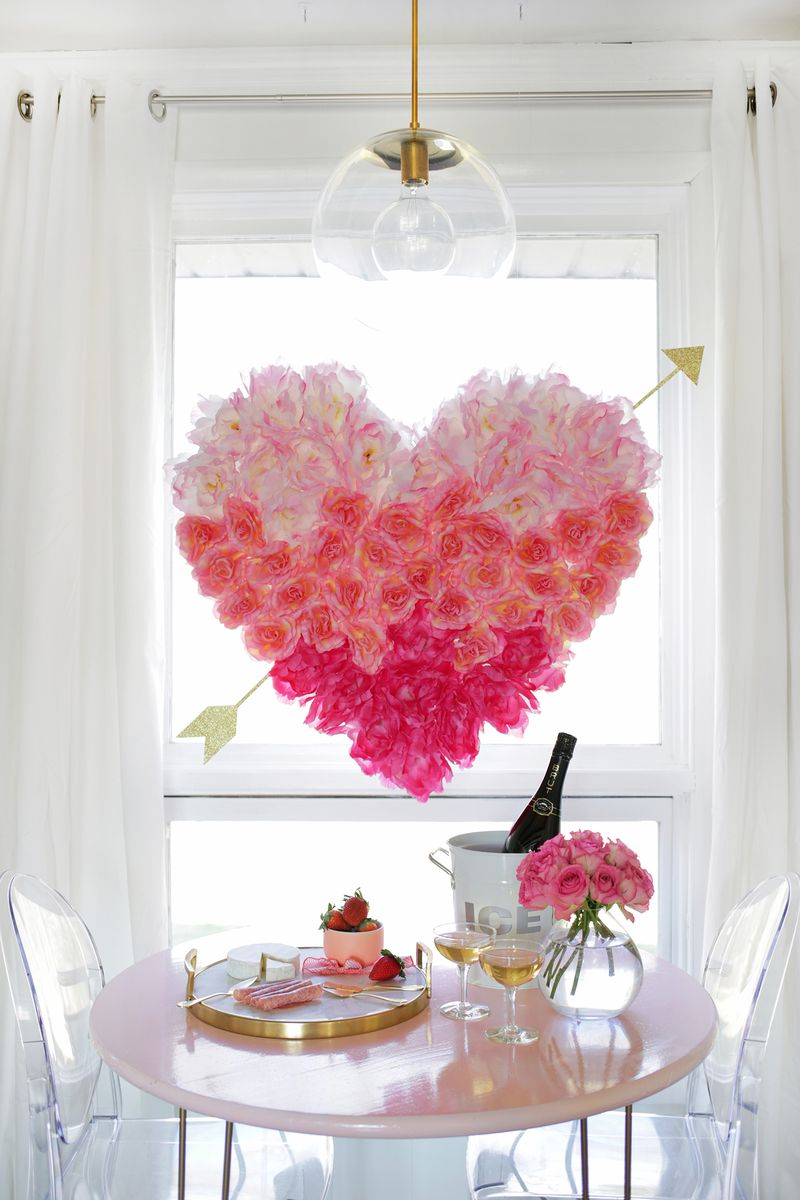 large pink flower heart with gold arrow coming out hanging above small 2 seat table. clear vase with pink flowers 2 glasses filled and an ice bucket with bottle of drink