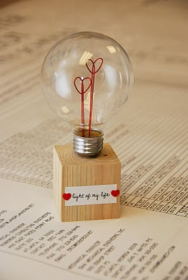 round light bulb with 2 wire red hearts on a wood block that has a paper saying light of my life